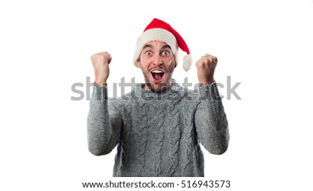 A young successful man with an Santa Claus hat with his arms raised celebrating cheering shouting isolated on white background