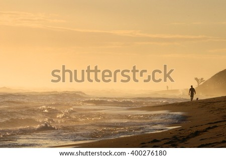 A young surfer goes with his dog on the beach during sunrise - stock photo