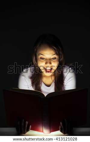 A young surprised woman in a dark environment reads a book that shines light from within. - stock photo