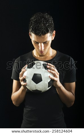 A young sweaty soccer player sweating on a low key setting with soccer ball. - stock photo