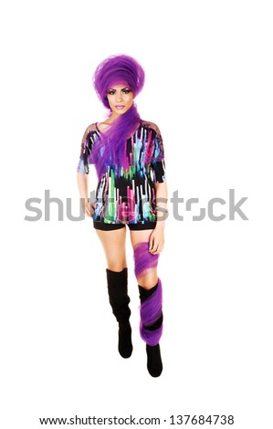 A young tall woman standing for white background in black shorts and long boots with lilac twill around her head and body.