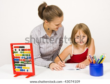 A young teacher, or mother, smiling and learning together with a little girl against white wall - educational tools and objects on the table. - stock photo