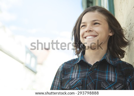 A Young teen posing outdoors with an urban background - stock photo