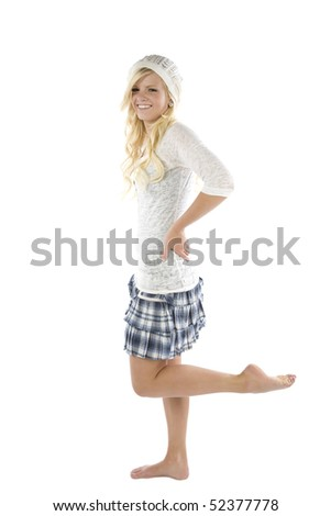 A young teenage girl in a blue skirt and white shirt standing with one leg up.