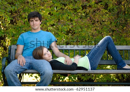 A young teenage girl is lying on a bench with her head on her boyfriend's lap. - stock photo