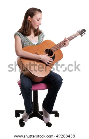 a young teenage girl sitting and playing a guitar