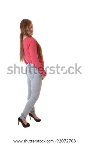 A young teenager in jeans and a red sweater and high heels standing in the studio, with her long brunette hair, for white background. - stock photo