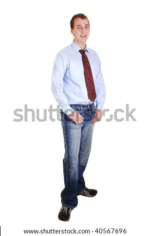 A young teenager in jeans and blue dress shirt with tie standing in the studio for white background isolated.