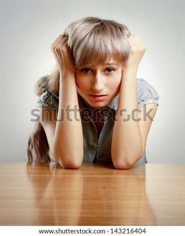 A young tired woman sitting at the desk, isolated on grey - stock photo