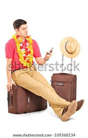 A young tourist typing a sms seated on a travel bag while waiting isolated on white background - stock photo