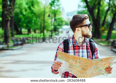 A young tourist with a beard holding a map and looking to the side in the alley in the park - stock photo