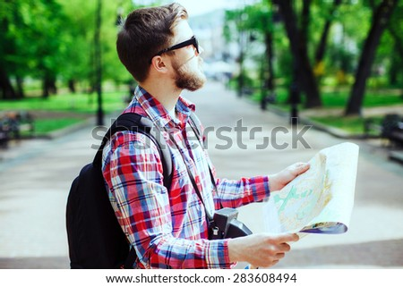 A young tourist with a beard holding a map and looking to the side in the alley in the park, profile - stock photo