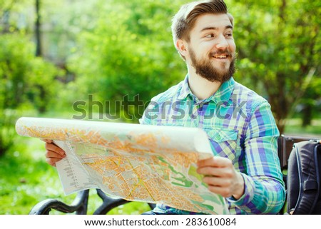 A young tourist with a beard laughing and sitting on a bench in the park, looking at the map, close-up - stock photo