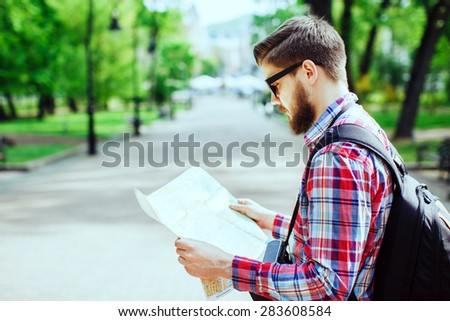 A young tourist with a beard looking to the map in the alley in the park, profile - stock photo