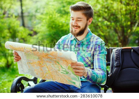 A young tourist with a beard smiling and sitting on a bench in the park, and looks at the city map - stock photo