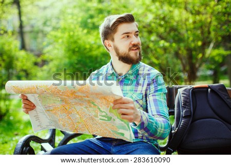 A young tourist with a beard smiling and sitting on a bench in the park, holding a map and looking to the side - stock photo