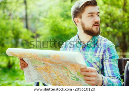 A young tourist with a beard smiling and sitting on a bench in the park, holding a map and looking to the side, close-up - stock photo