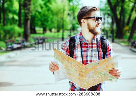 A young tourist with a beard smiling, holding a map and looking to the side in the alley in the park - stock photo