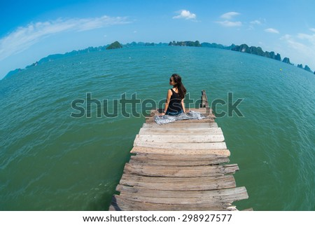 A young traveler girl sit on the wooden bridge in Halong bay and enjoy the beauty of seascape.