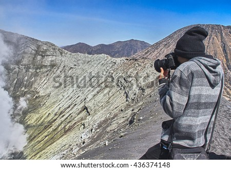 A young traveler try to take photograph at crater of Bromo vocalno, East Java, Indonesia.  - stock photo