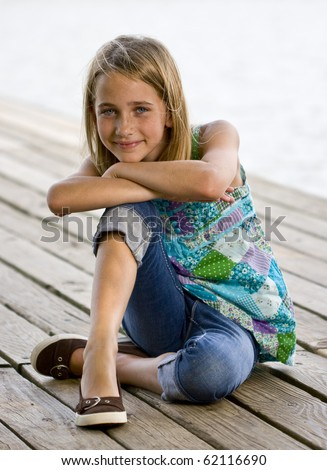 A young tween on a pier smiling at the camera - stock photo