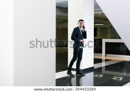 A young university graduate in suit standing in modern black and white interior, talking on mobile phone