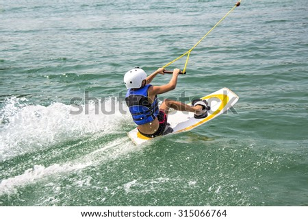 A young wakeboarder in action on the lake - stock photo