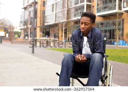 a young wheelchair user looking worried.  - stock photo
