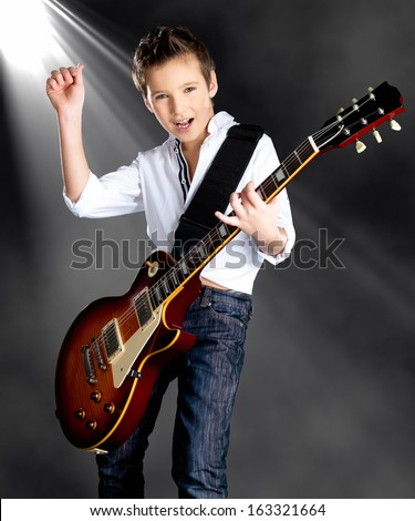 A young white boy sings and plays on the electric guitar on the stage with bright lights - stock photo