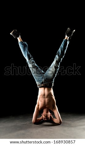 A young white Caucasian male stands on his head upside down doing a yoga inversion in the studio.