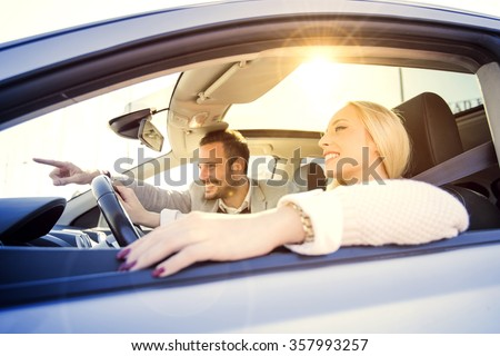 A young woman and a young man are laughing in the car, enjoying in the road trip. The woman is driving.