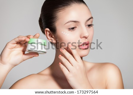A young woman applying anti-wrinkle cream