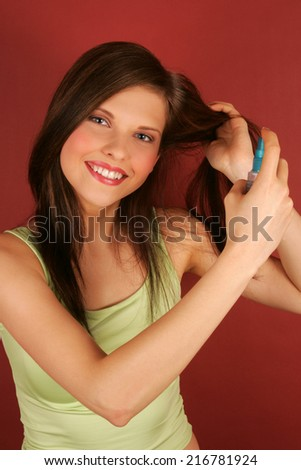 A young woman applying hairspray.