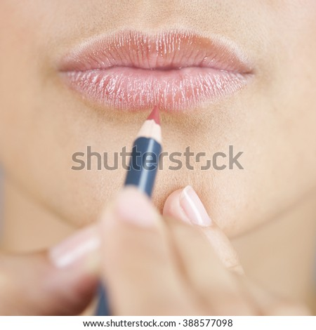 A young woman applying lip liner