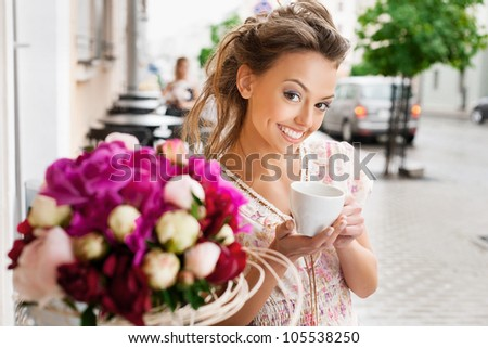 A young woman are drinking espresso. Holding a cup of espresso. Outdoors - stock photo