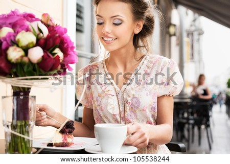 A young woman are eating a dessert. Holding a cup of tea. Outdoors
