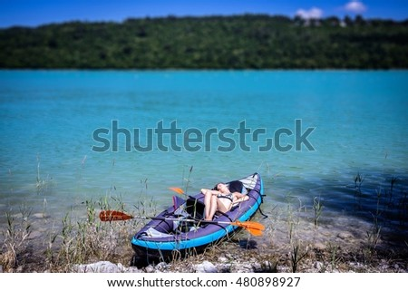a young woman asleep in his canoe on a blue lake