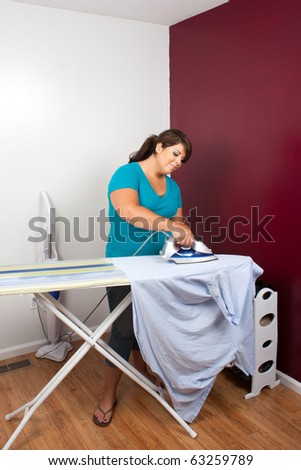 A young woman at home pressing some clothes on an ironing board.