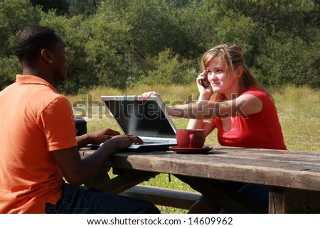 a young woman attempts to demand attention from a man working on his laptop computer outside