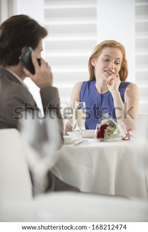 a young woman bored at the restaurant while her husband phone