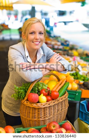 a young woman buying fruits and vegetables at a market. fresh and healthy food. - stock photo