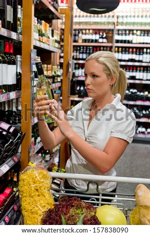 a young woman buying wine in a wine shop. - stock photo