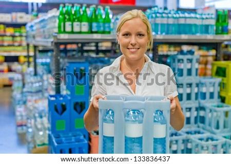 a young woman buys bottled water in the beverage department at the grocery store.