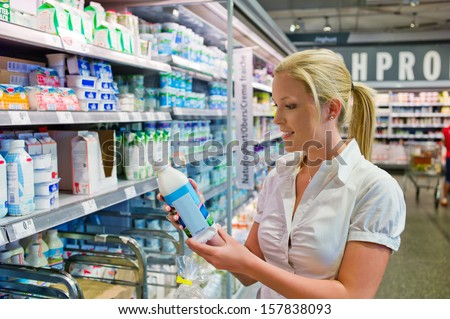 a young woman buys milk in a supermarket. fresh food from the refrigerated section