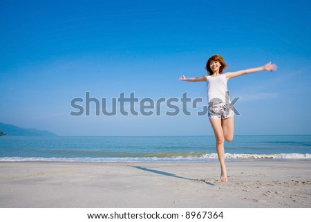 a young woman by the beach happy jumping