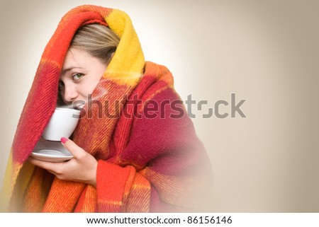 A young woman caught a cold, wrapped in a blanket and something hot drink from a cup. - stock photo