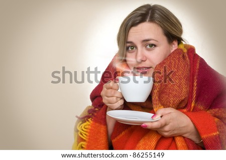 A young woman caught a cold, wrapped in a blanket and something hot drink from a cup.