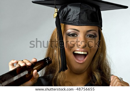 A young woman celebrating her graduation with a bottle of beer. - stock photo