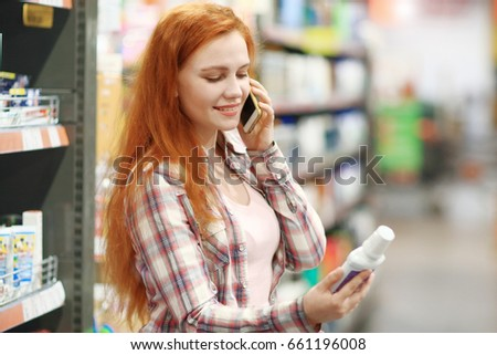 A young woman chooses the goods in the supermarket