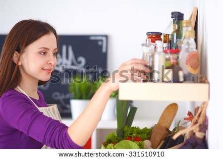 A young woman choosing spices in her kitchen . - stock photo